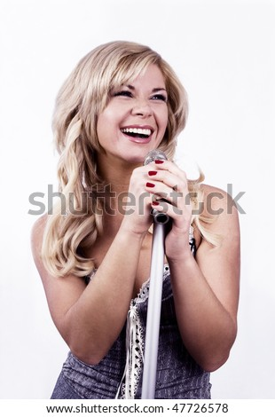 Pretty girl singing into microphone.  Young female singer with blond hair singing a song. Woman laying down some vocal tracks. Leader of pop music band on white background. - stock photo
