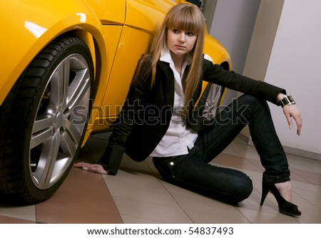 Pretty girl sitting against of yellow sport car - stock photo