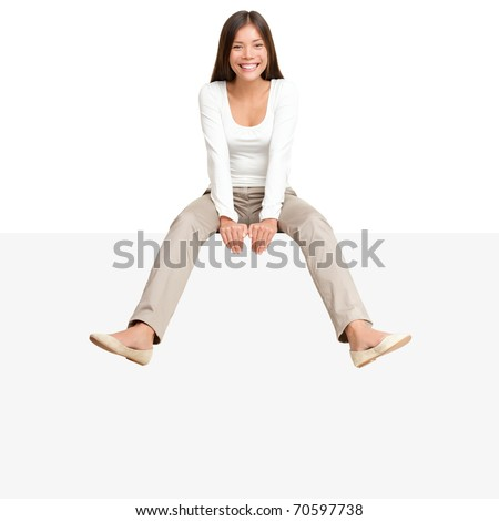 Pretty girl sitting casual on big blank billboard poster sign with lot of copy space. Smiling asian caucasian young woman model. Isolated on white background - stock photo