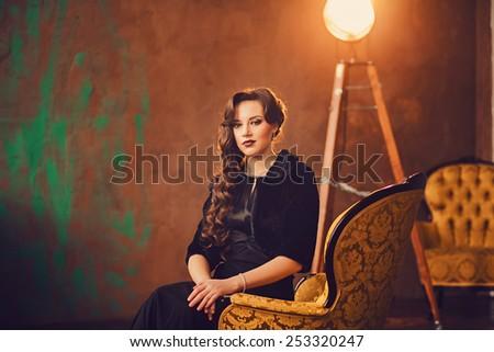 Pretty girl sitting on a chair in a retro interior - stock photo