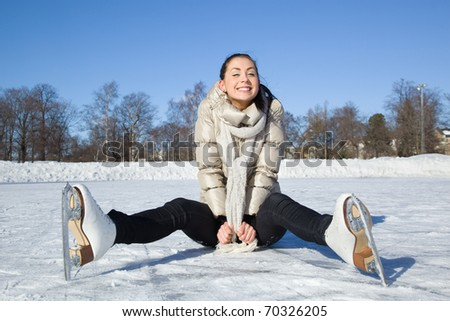 Pretty girl sitting on ice - stock photo