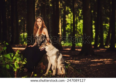 Pretty girl sitting with a dog in the dark forest - stock photo