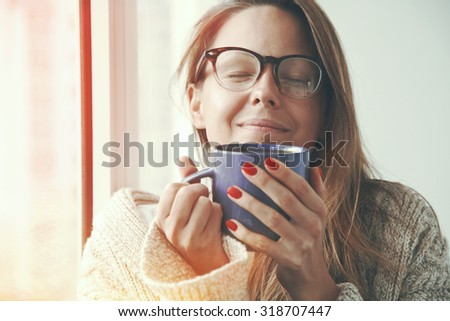 pretty girl smelling coffee aroma in morning sunlight - stock photo