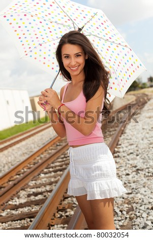 Pretty girl standing by a railroad track holding a colorful white polka dot umbrella. - stock photo