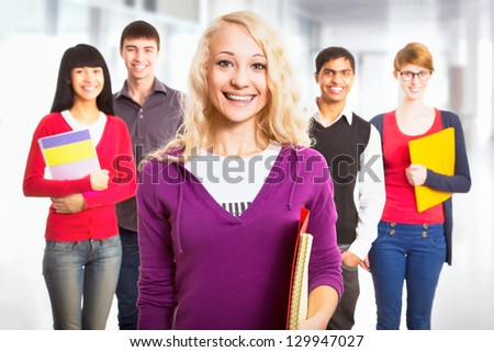 Pretty girl student and her diversity friends on background - stock photo