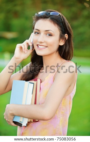 pretty girl-student holds a book and talking on a cell phone on the natural background - stock photo