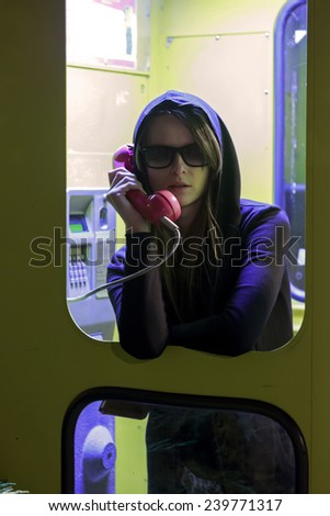 Pretty girl talking by the payphone in telephone booth, Europe  - stock photo