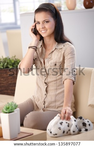 Pretty girl talking on mobile phone at home, smiling. - stock photo