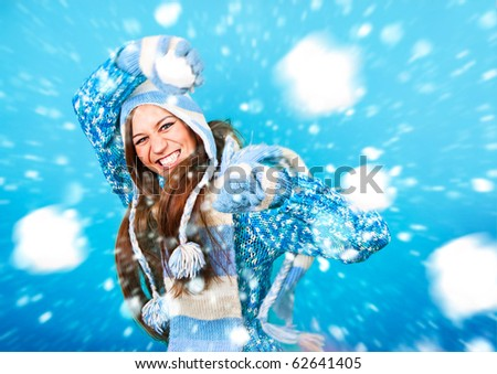 pretty girl throwing a snowball - stock photo