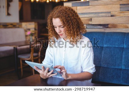 Pretty girl using a small tablet at table in a cafe - stock photo