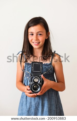Pretty girl using an old film camera - stock photo