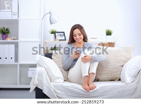 Pretty girl using her smartphone on  couch at home in the living room - stock photo