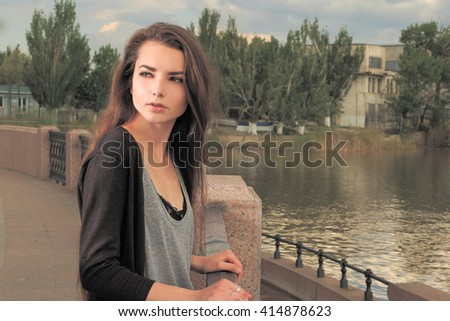 Pretty girl waiting for your. Wearing light gray shirt, black jacket, an young american woman standing by metal fence on pier in New York, frowned,sad,depressed,unhappy,looking back. Instagram effect. - stock photo