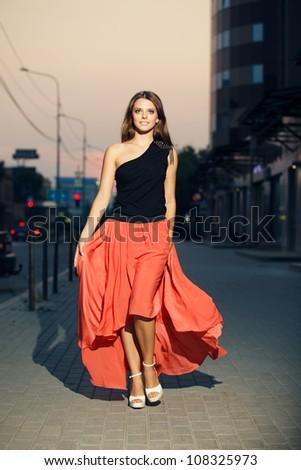 Pretty girl walks on the street - stock photo