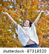 Pretty girl waving arms in air during fall - stock photo