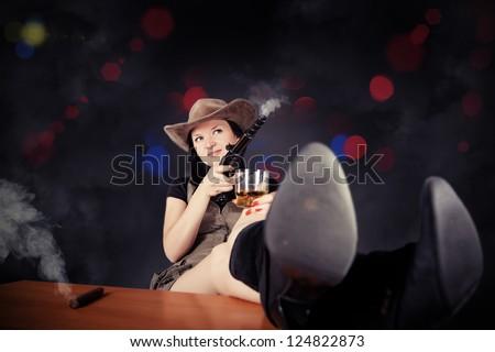 pretty girl with a gun cowboy drink whiskey - stock photo
