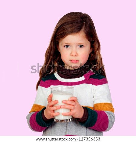 Pretty girl with a milk glass isolated on a pink background - stock photo