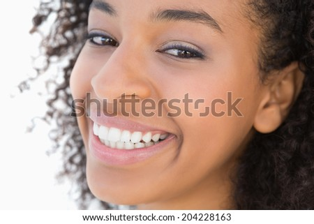Pretty girl with afro hairstyle smiling at camera on white background - stock photo