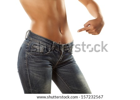 pretty girl with bare belly in tight jeans shows a finger on her stomach - stock photo