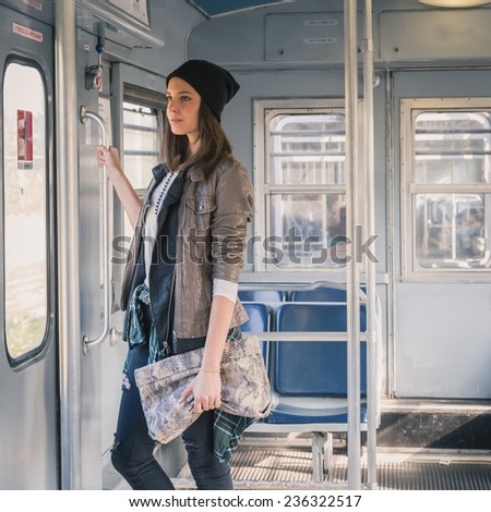 Pretty girl with beanie posing in a metro car - stock photo