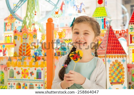 Pretty girl with beautiful eyes blinking at camera and holding lollipop in hands - stock photo