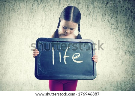 Pretty girl with braids holding board with an inscription Life - stock photo