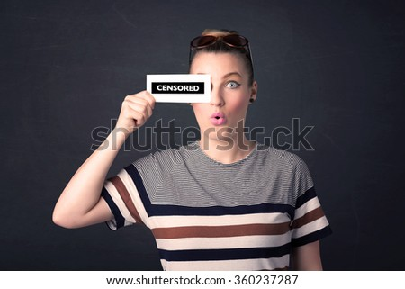 Pretty girl with censored paper sign holding in hand - stock photo