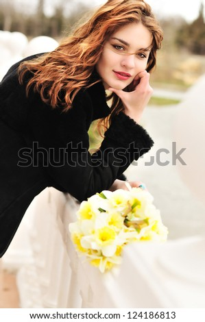 pretty girl with daffodils in windy spring day - stock photo