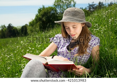 Pretty Girl With Daisy Flower In Her Mouth Enjoying Reading Interesting Book In Beautiful Park On Sunny Day - stock photo