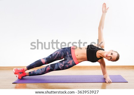 Pretty girl with dark hair wearing pink snickers, dark leggings and black short top doing side plank on one hand at gym, fitness, white wall and wooden floor. - stock photo