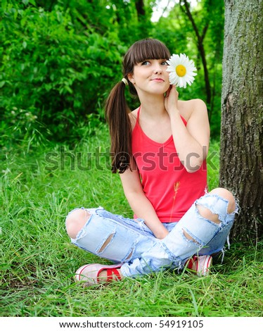 pretty girl with flowers in her hair sitting on a grass - stock photo