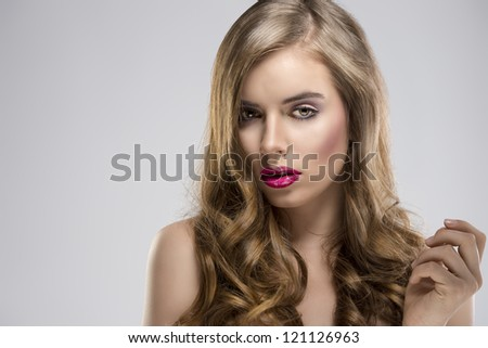 pretty girl with flowing wavy hair and purple make-up, she is turned of three quarters at right and looks in to the lens - stock photo