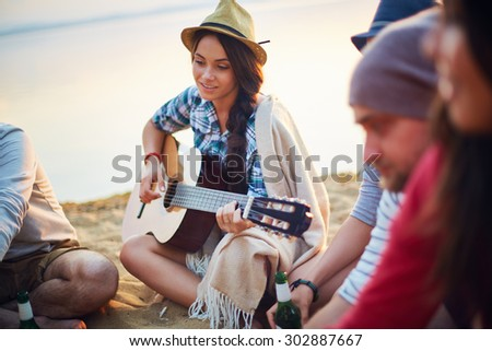 Pretty girl with guitar sitting on sandy beach among her friends - stock photo