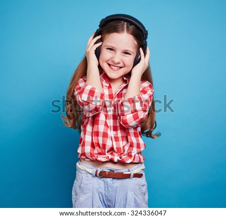 Pretty girl with headphones looking at camera and enjoying music - stock photo