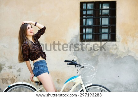 Pretty girl with long fair hair wearing on dark blouse and blue shorts is sitting on the bicycle and have fun on the old wall background - stock photo
