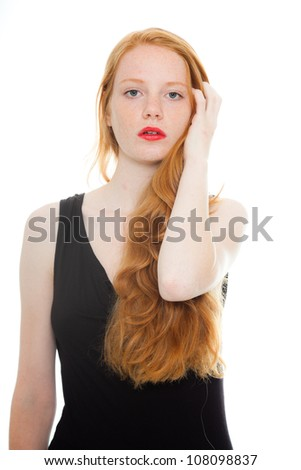 Pretty girl with long red hair and lipstick wearing black shirt. Fashion studio shot isolated on white background. - stock photo
