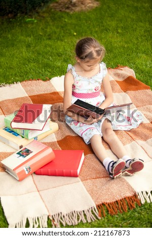 Pretty girl with photo album sitting on plaid at park - stock photo