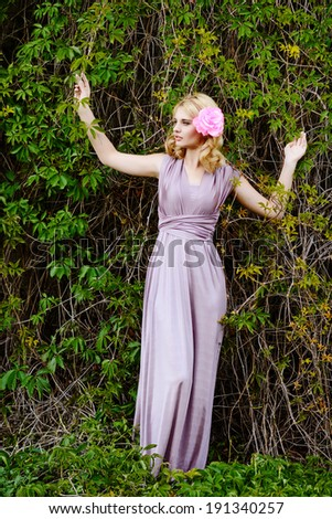 pretty girl with rose in hair near the woody vine - stock photo