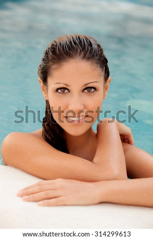 Pretty girl with wet hair in the pool smiling. - stock photo