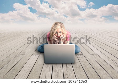 Pretty girl working on a laptop on a wood floor and a cloudy blue sky. - stock photo