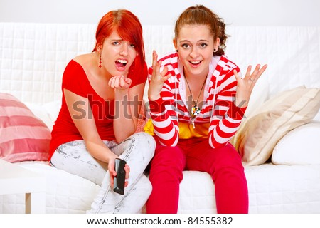 Pretty girlfriends upset by TV program - stock photo