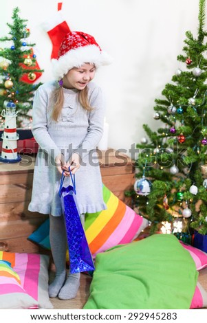 Pretty girls laughing with a gift in hand next to Christmas tree - stock photo
