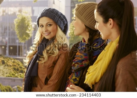 Pretty girls walking on the street together, smiling, chatting. - stock photo
