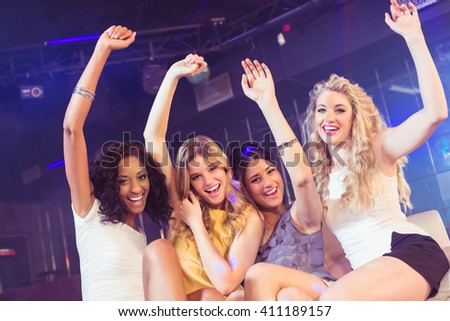 Pretty girls with arms up in a nightclub - stock photo
