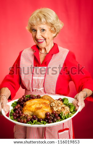 Pretty grandmother serving holiday turkey dinner.  Red background. - stock photo