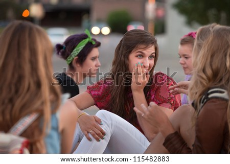Pretty group of European girls whispering with each other - stock photo