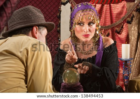 Pretty gypsy lady pointing with finger over crystal ball - stock photo