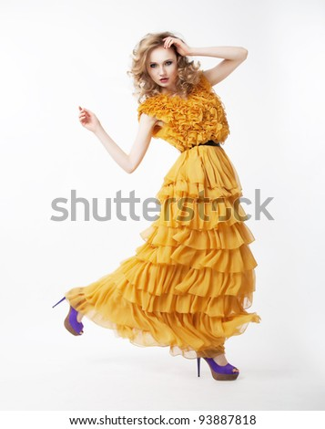 Pretty happy active female blond hair woman in yellow prom dress posing. Fashion style. Studio shot - stock photo