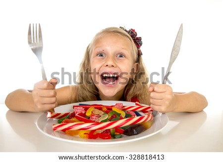 pretty happy Caucasian female child eating dish full of candy holding fork and knife  in sweet sugar abuse dangerous diet and unhealthy nutrition concept isolated on white background - stock photo