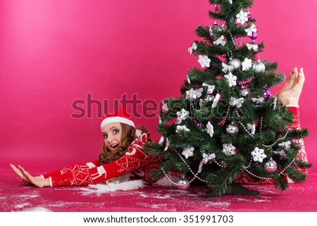 Pretty happy girl is lying behind christmas tree isolated on red - stock photo